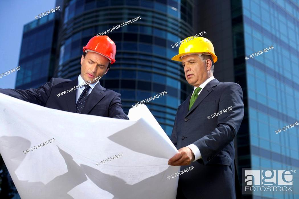 Stock Photo: Two Businessman with hardhats watching a plan.