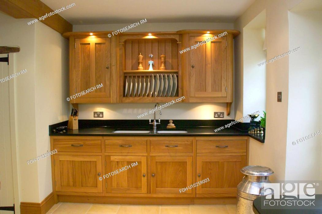 Stock Photo Recessed Lighting And Ed Cupboard With Plate Rack Above Sink Set Into Wood Kitchen Unit