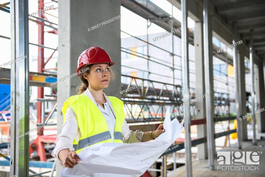 Stock Photo: Female architect with blueprint at construction site.