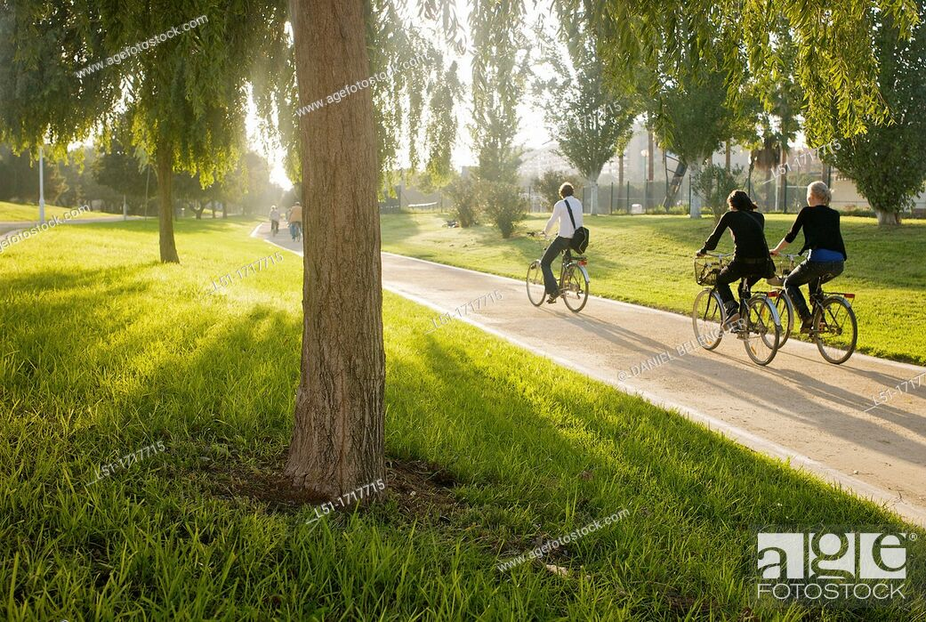 Stock Photo: people cycling by the Turia park, Valencia, Spain.