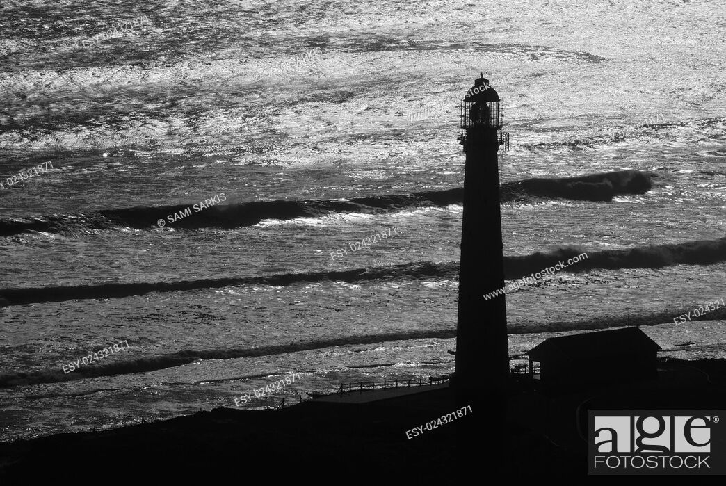 Stock Photo: Lighthouse silhouette by ocean, Western Cape Province, South Africa.
