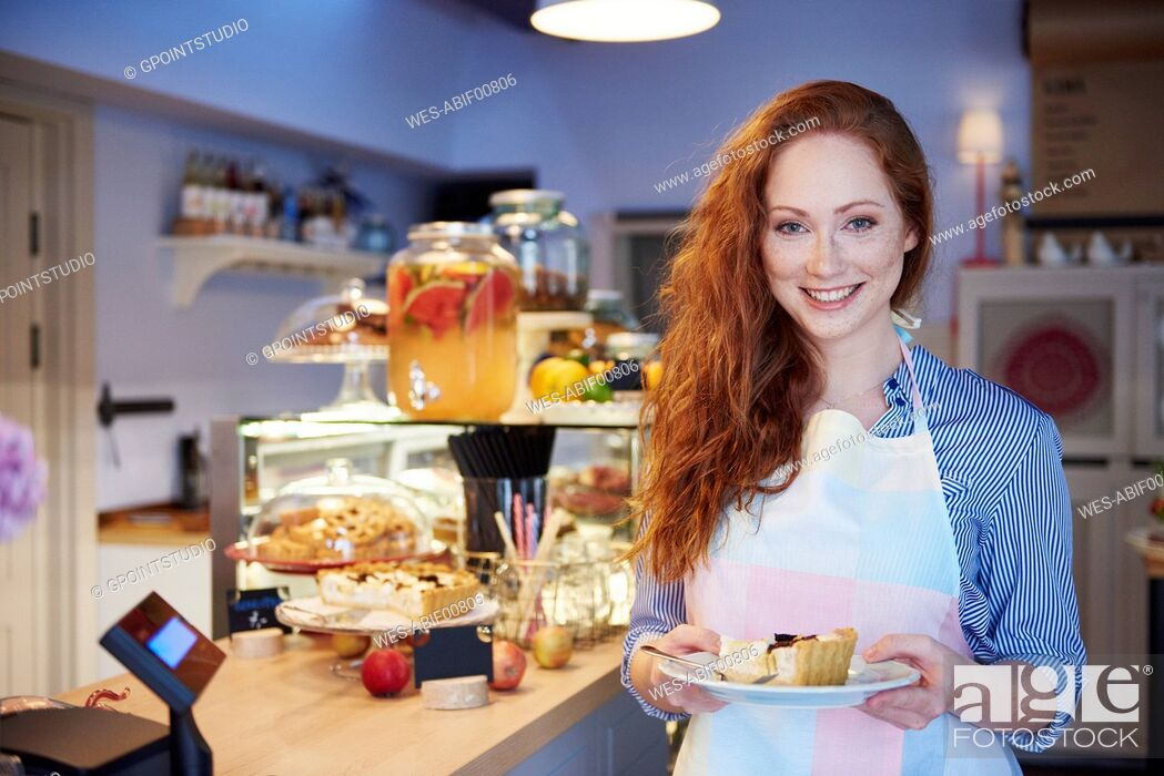 Imagen: Portrait of smiling young woman serving cake in a cafe.