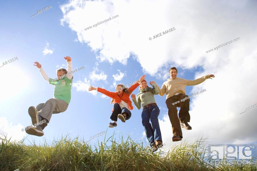 Stock Photo: Family of four jumping on grass outdoors, low angle view.