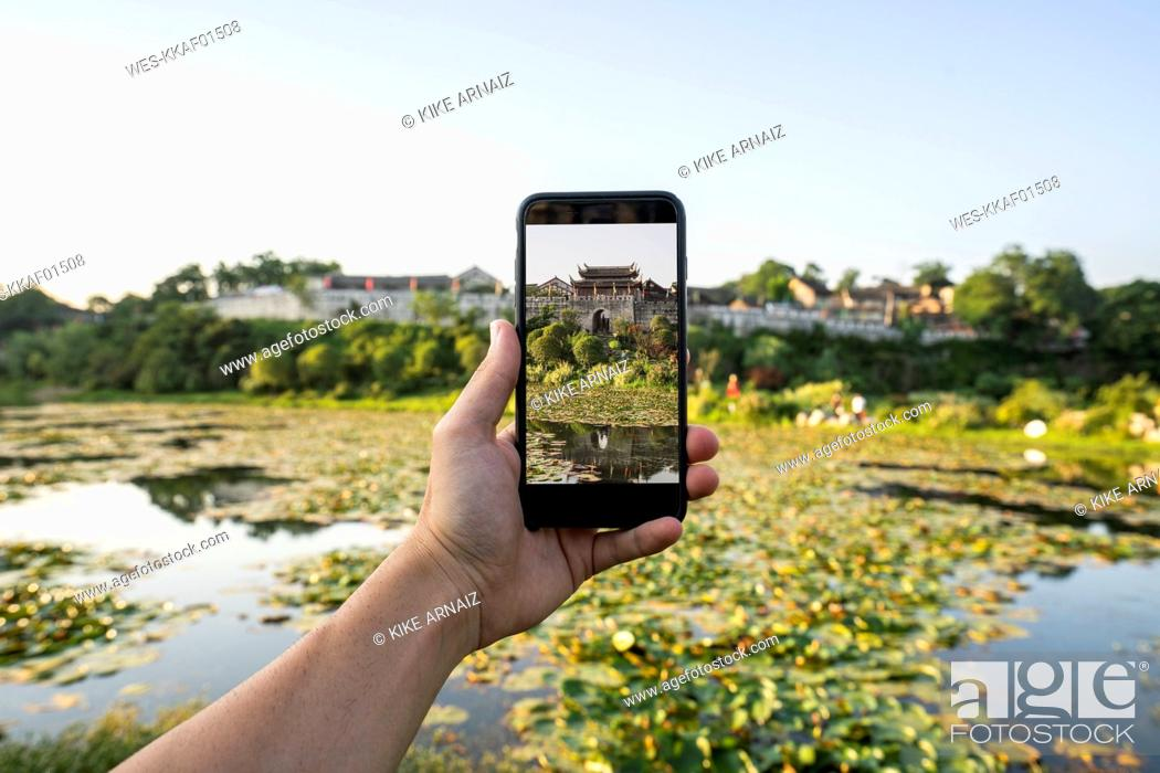 Stock Photo: China, Qinyang, man holding smartphone, picture.