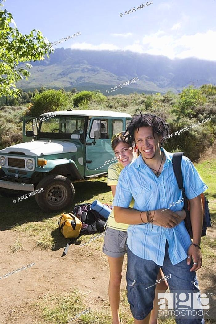 Stock Photo: Young couple standing near parked jeep at start of camping holiday, woman embracing man, smiling, portrait.