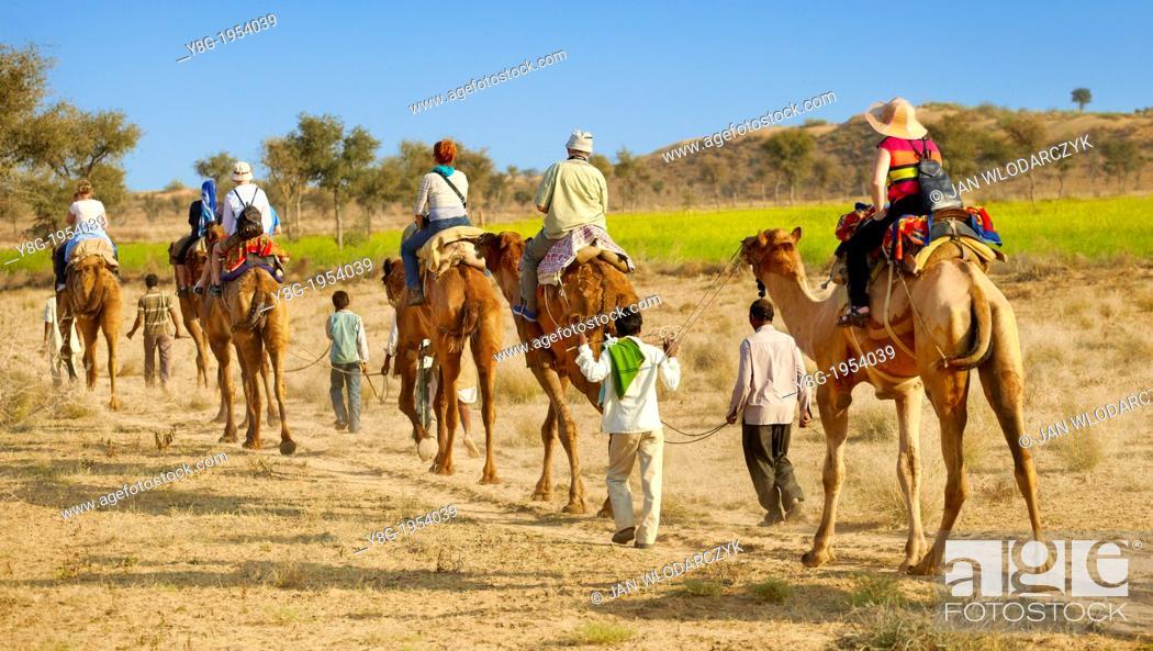 Stock Photo: Camel caravan safari ride with tourists in Thar Desert near Jaisalmer, India.