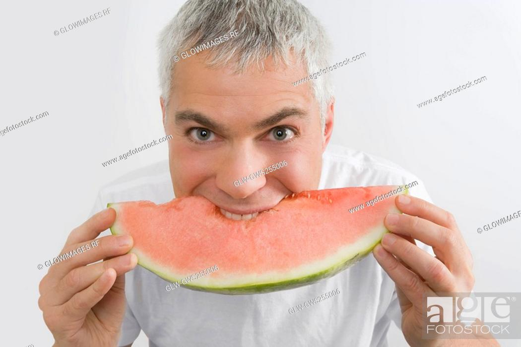 Stock Photo: Portrait of a mature man eating a slice of watermelon.