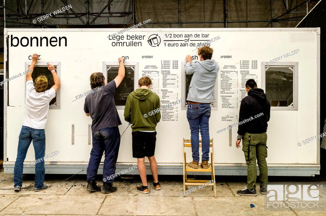 Stock Photo: People removing a pricelist from the side of a portacabin at the end of a music festival (Ghent, Belgium). The sign reads 'Empty cup exchange'.