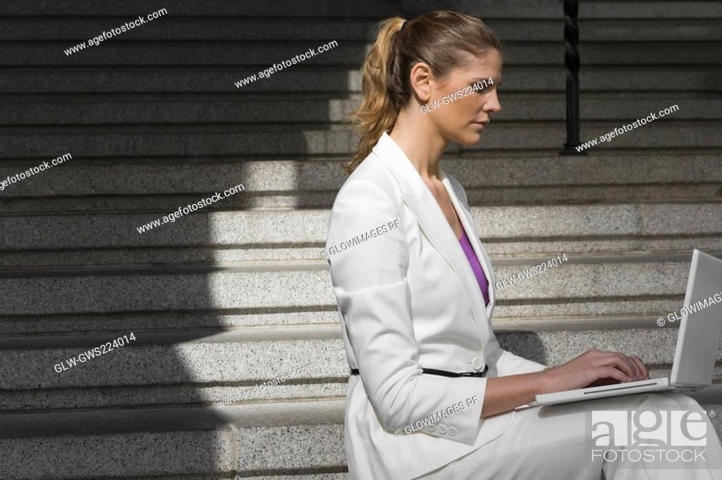 Stock Photo: Side profile of a businesswoman sitting on a staircase and using a laptop.