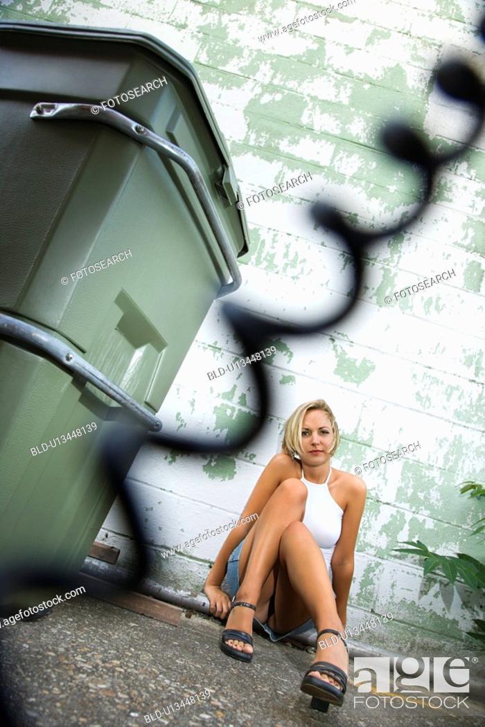 Stock Photo: Woman sitting on a street in an urban setting.
