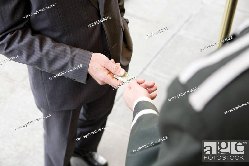 Stock Photo: Businessman tipping bellhop.