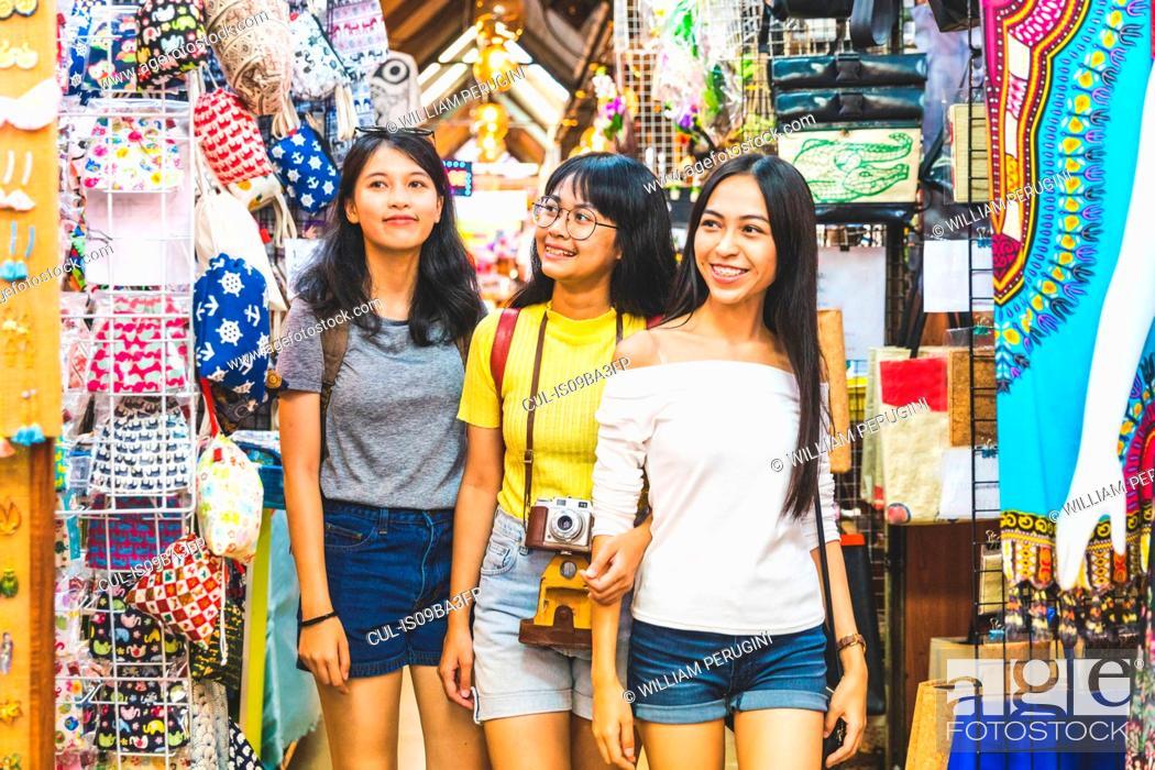 Stock Photo: Tourists walking in bazaar, Bangkok, Thailand.