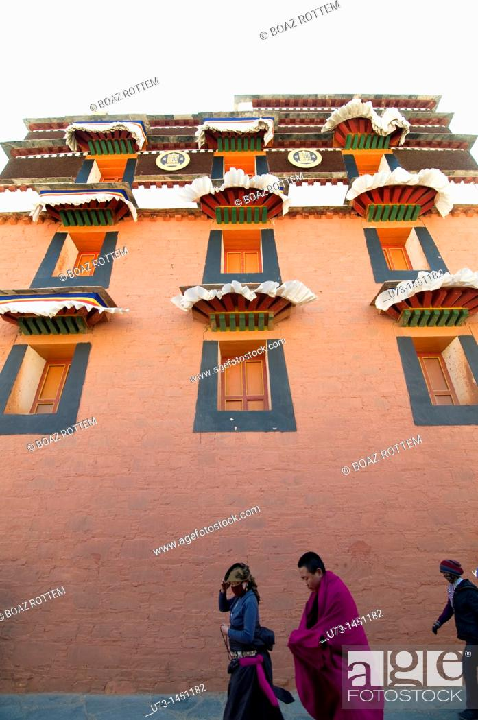 Stock Photo: Tibetan pilgrims and a monk walking by one of Labrang monastery complex temples.