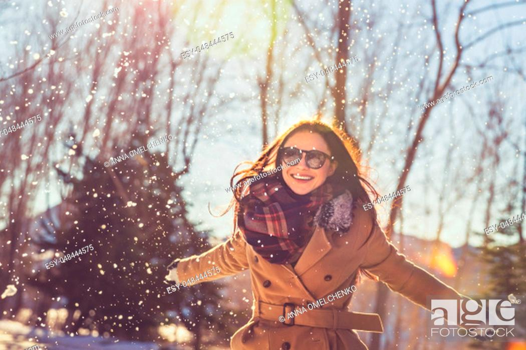 Stock Photo: Portrait of a pretty girl with pleasure spending time on bright sunny day in winter park, having fun like a child, happy wintertime vacation.