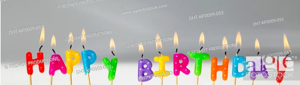 Stock Photo: Coloured letter Candles lit up and spelling out Happy Birthday.