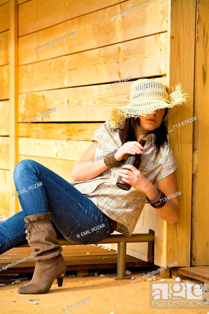 Stock Photo: Drunk young woman is sitting with a beer bottle in hands.