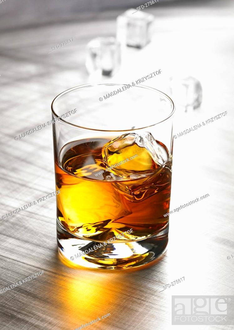 Stock Photo: Glass of whisky with ice cubes.