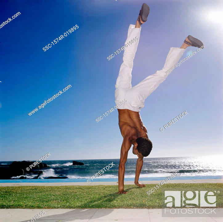 Stock Photo: Young man doing a handstand on the grass.