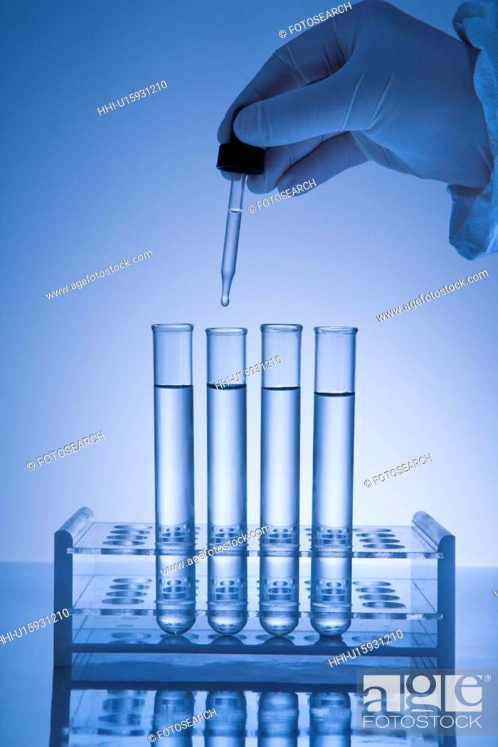 Stock Photo: Hand holding dropper over test tubes.
