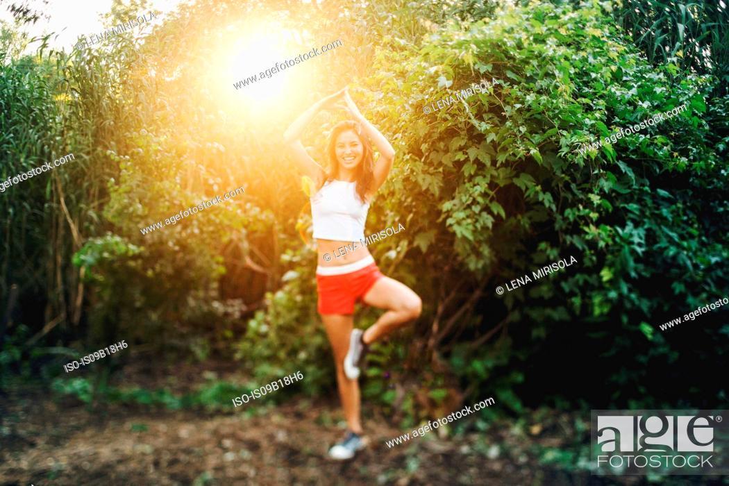 Stock Photo: Young woman practising yoga at sunset.