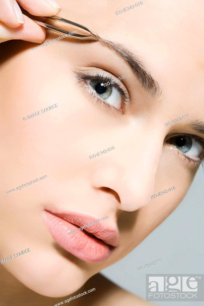 Stock Photo: Woman plucking eyebrow.