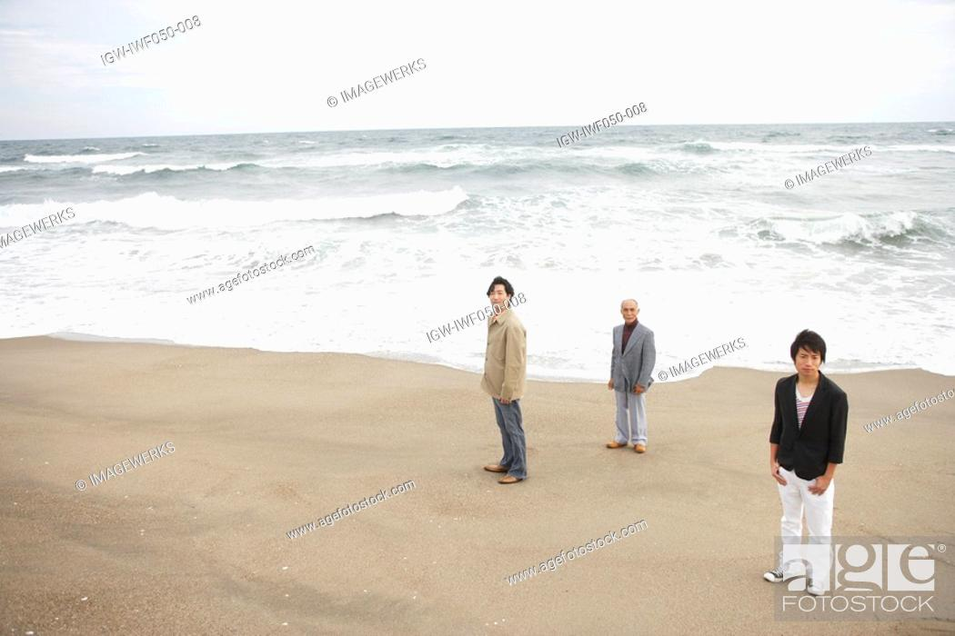 Stock Photo: Son with father and grandfather standing at beach.
