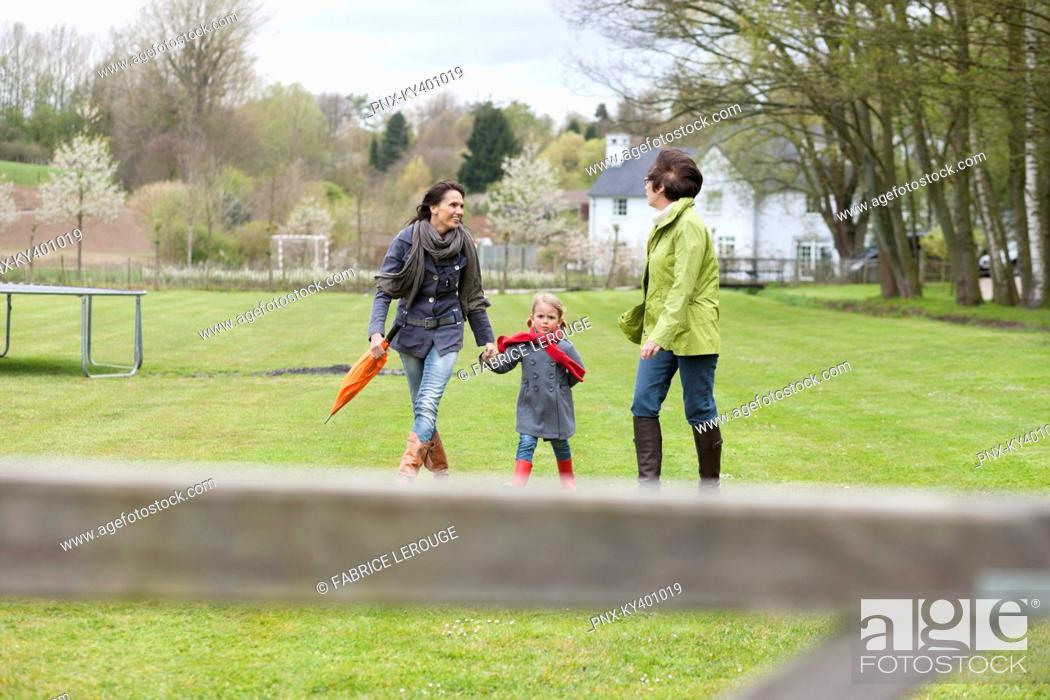 Stock Photo: Girl walking with her mother and grandmother in a lawn.