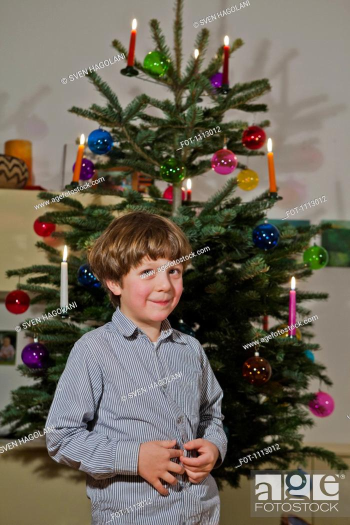 Stock Photo: A young boy standing in front of a decorated Christmas tree.