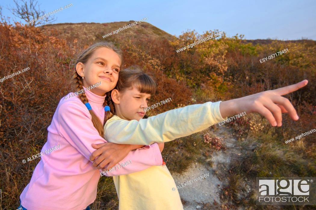 Stock Photo: The girl hugs her sister who points her finger into the distance.