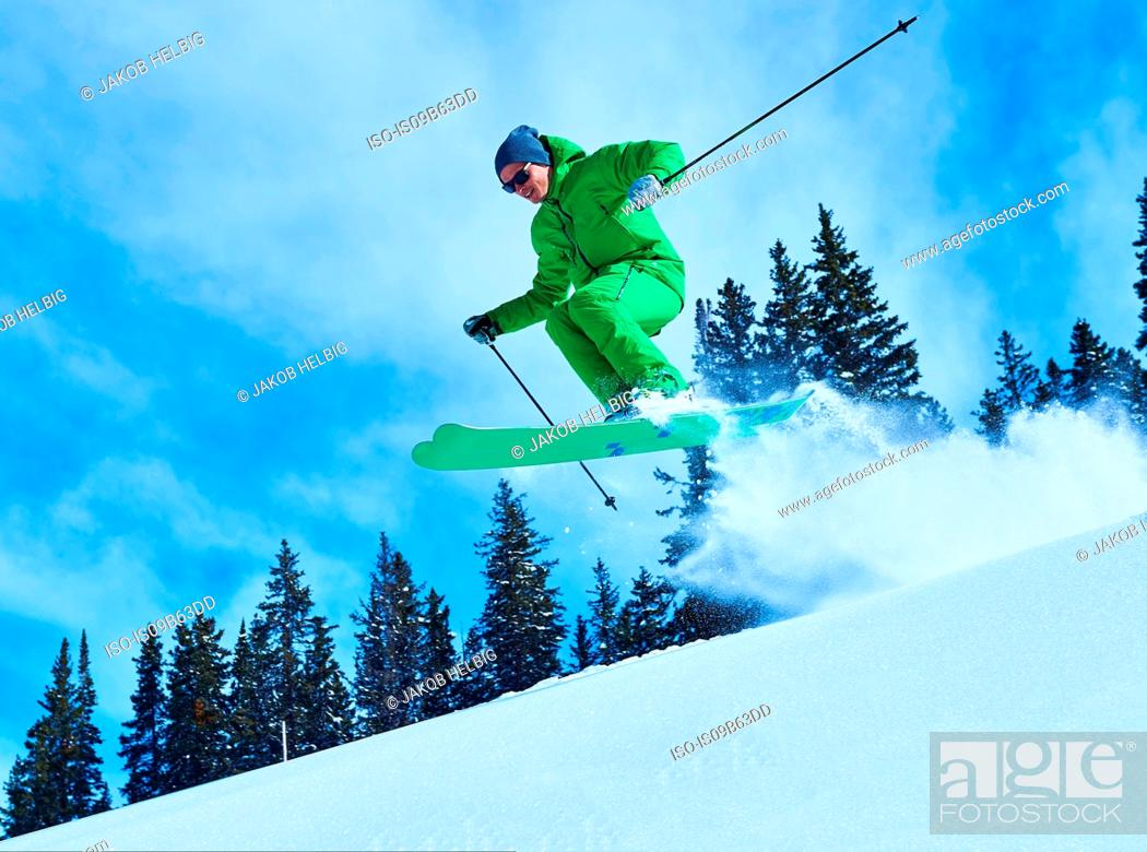 Photo de stock: Man jumping while skiing down snow covered mountainside, Aspen, Colorado, USA.