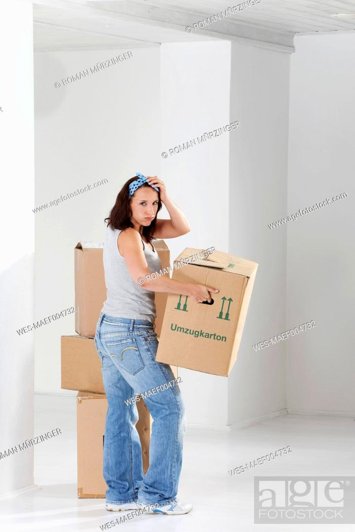 Stock Photo: Young woman carrying on cardboard box, portrait.