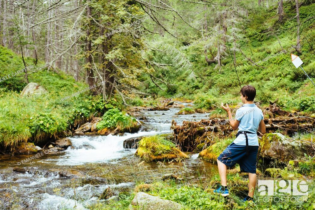 Stock Photo: boy child fishing in the river in the mountains in the alps in the summer.