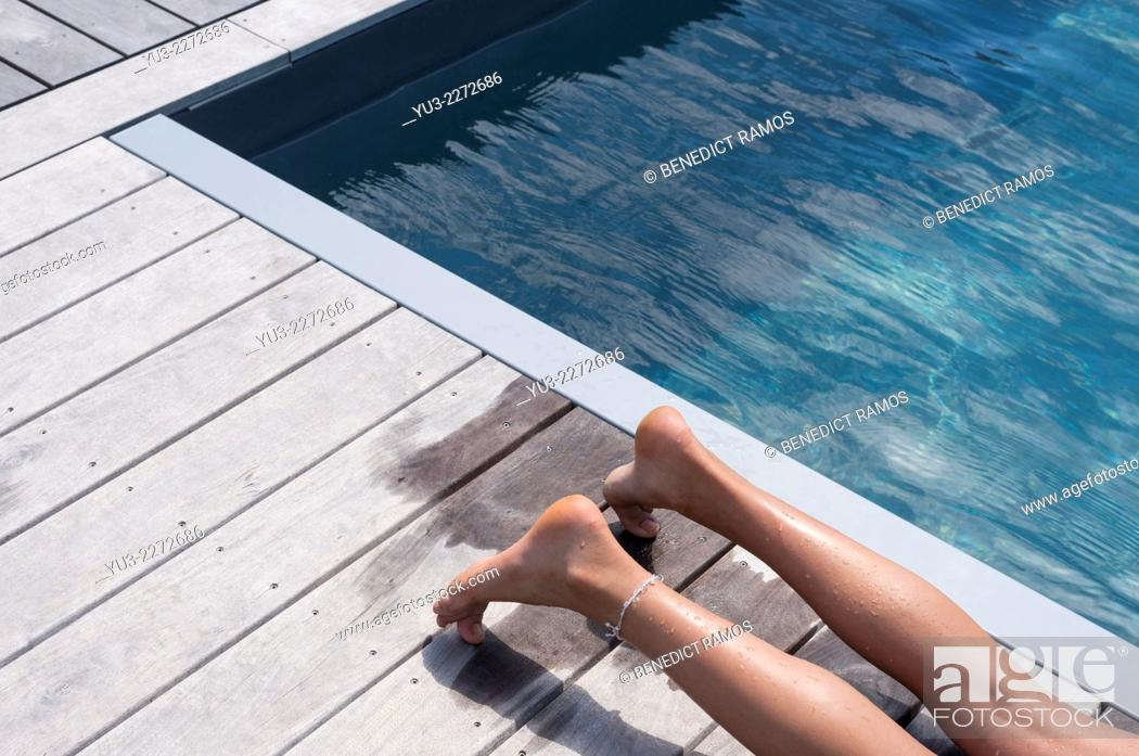 Stock Photo: Girl's legs lying on decking by swimming pool.