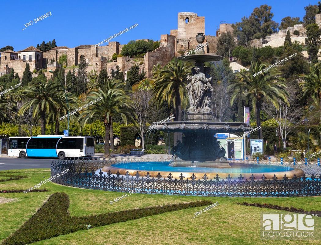 Stock Photo: Fountain (El fuente de tres gracias) on the roundabout entering paseo Parque with the Alcazaba in the background - Malaga, Spain.