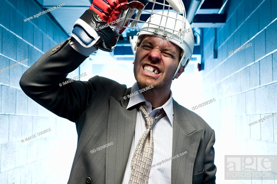 Stock Photo: Grimacing businessman in a sports helmet.
