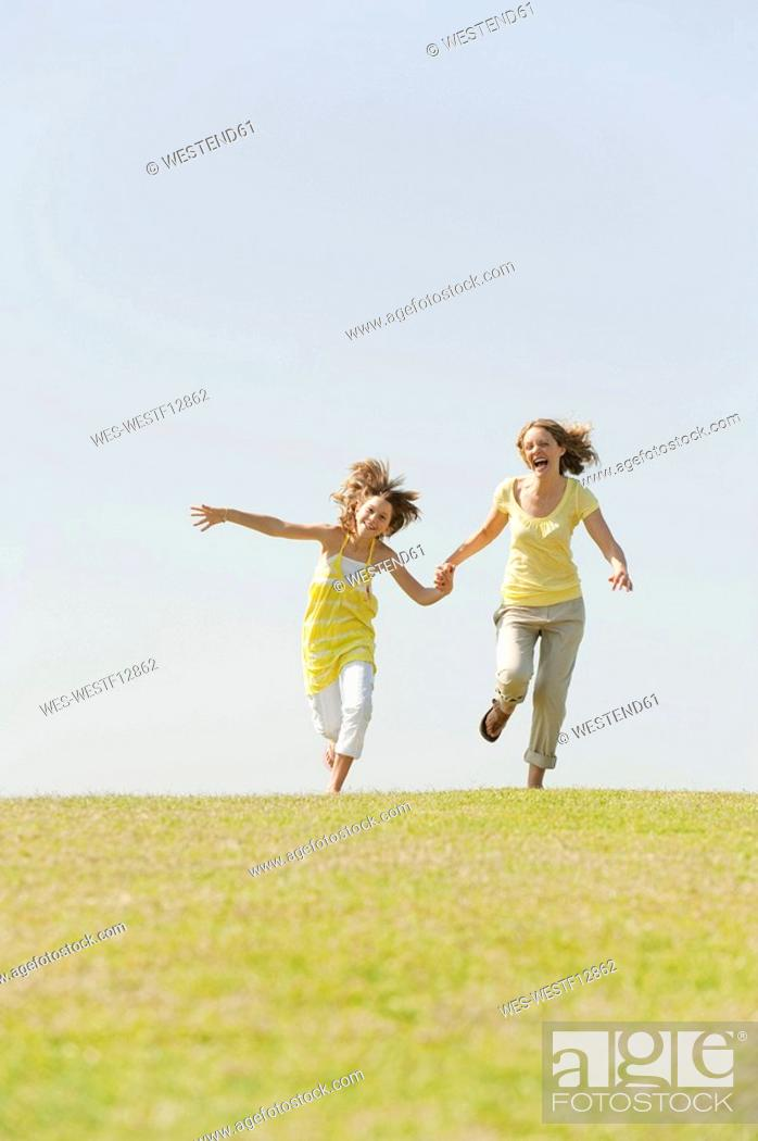 Stock Photo: Spain, Mallorca, Mother and daughter 10-11 running in meadow.
