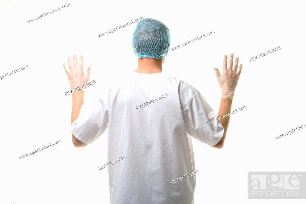 Stock Photo: A male doctor stands with his hands raised up, gloves are on, a mask and a hat are on his head, rear view.