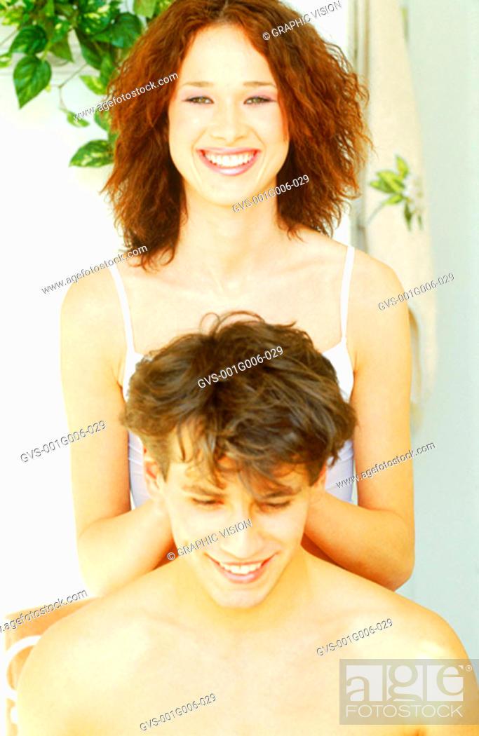 Stock Photo: Young woman giving a man a neck rub.