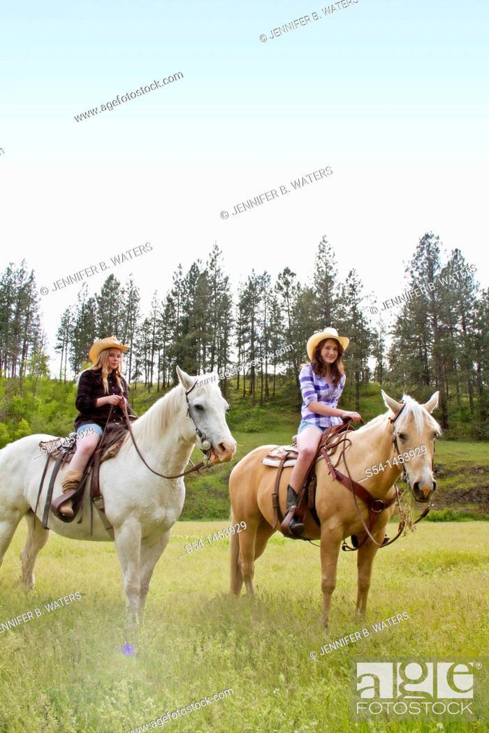 Stock Photo: Two teen girls riding horses in Reardan, Washington, USA.