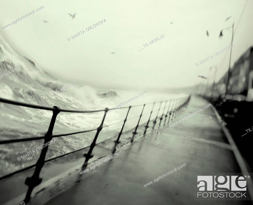 Imagen: Storm at the coast with waves crashing against the promenade.