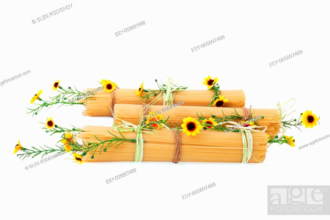 Stock Photo: Uncooked Italian spaghetti decorated with yellow flowers isolated on white background.