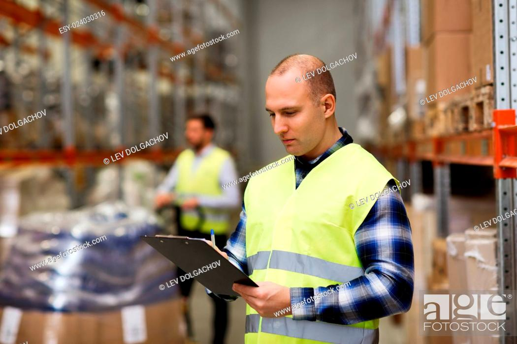 Stock Photo: wholesale, logistic, people and export concept - man with clipboard in reflective safety vest at warehouse.