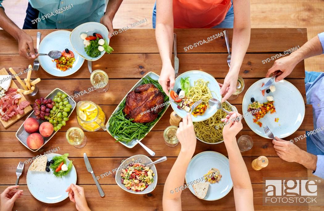 Stock Photo: group of people eating at table with food.