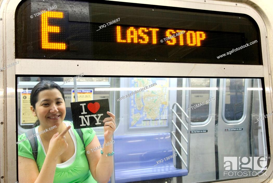 Imagen: Hispanic, Asian, woman holding 'I Love New York' postcard, Subway train metro station, New York City.