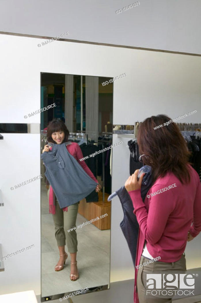 Stock Photo: Young woman in clothes store.