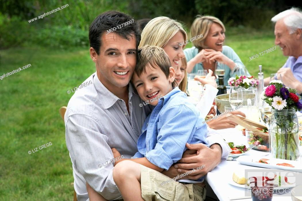 Stock Photo: Family dining at table in garden father and son 7-9 looking at camera.