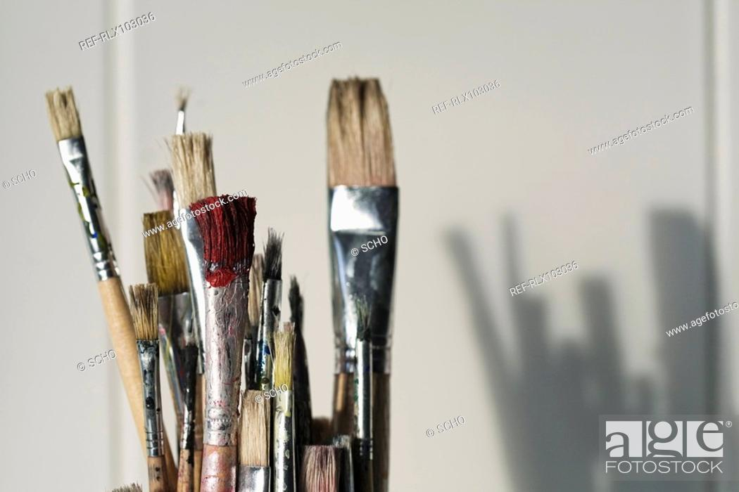 Stock Photo: Paintbrushes in Glass jar in classroom with shadow on tiles, close-up.