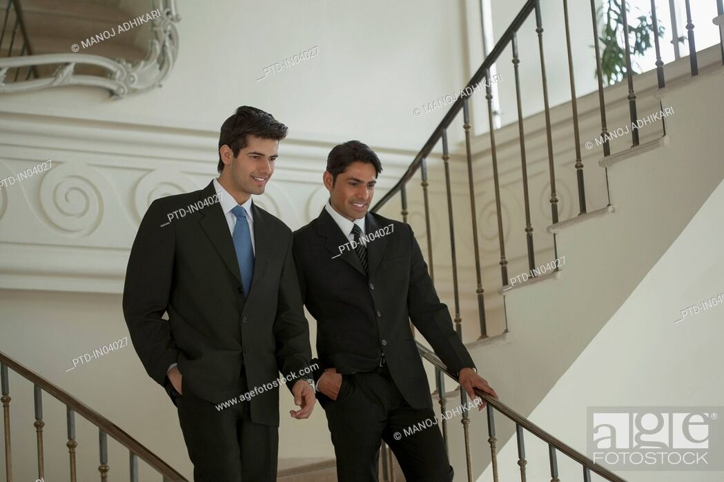 Stock Photo: India, Two businessmen walking down stairs.