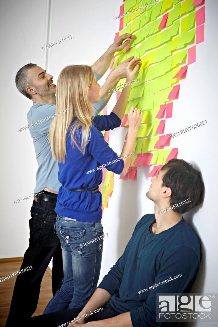 Stock Photo: Germany, Cologne, Men and woman sticking paper note on wall.