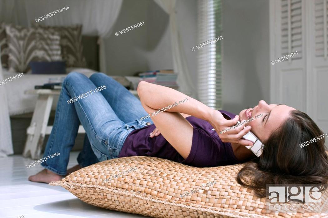 Stock Photo: Germany, Hamburg, Woman lying on bed using mobile phone.